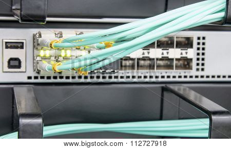 Fibre optic patch leads connected to a network distribution router with a shallow depth of field poster