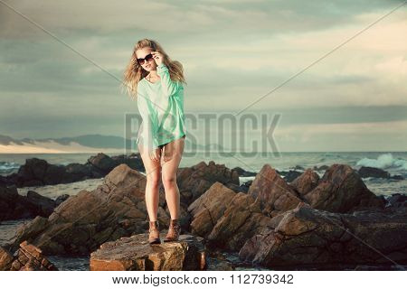 Blonde In Green Jersey Standing On A Rock On The Beach