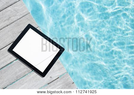 Tablet computer with empty screen on the wooden pool deck
