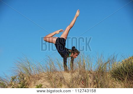 Gymnast Doing A Handstand On The Beach