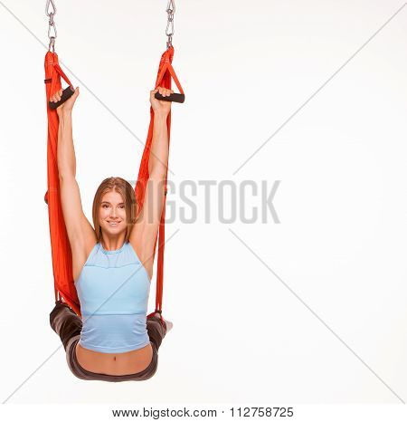 Young woman doing anti-gravity aerial yoga in hammock
