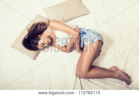 Woman Stomach Pain On Bed Top View