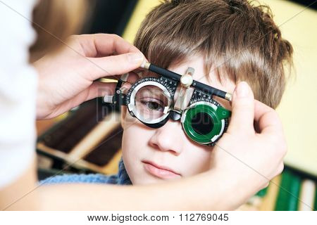 Optometry concept. Young boy with phoropter during sight testing or eye examinations in ophthalmological clinic