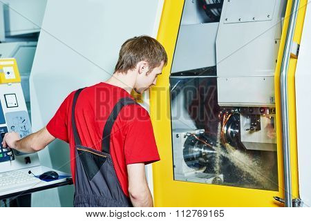 mechanical industrial worker at cnc milling machine center in tool manufacture workshop