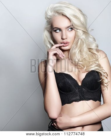 Fashion Photo Of A Beautiful Young Woman In A Black Bustier. Blonde Model  Posing In Studio.