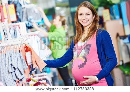 Pregnancy shopping. smiling pregnant woman choosing newborn clothes at baby shop store
