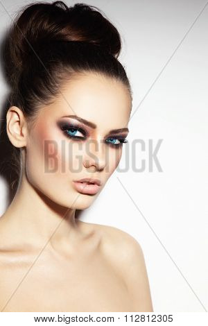 Young beautiful blue-eyed woman with smoky eyes and stylish hair bun