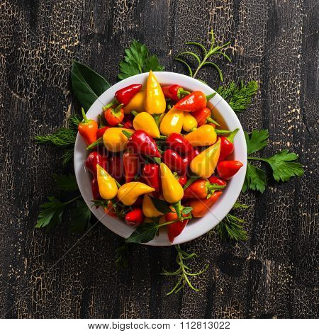 Top View Of Plate With Orange, Red And Yellow Hot Chili Peppers, Greenery On Cracks Black Background