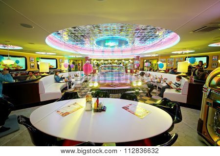 RUSSIAN, MOSCOW - JAN 18, 2015: People have a rest in Beverly Hills Diner restaurant with pink Cadillac in the middle.