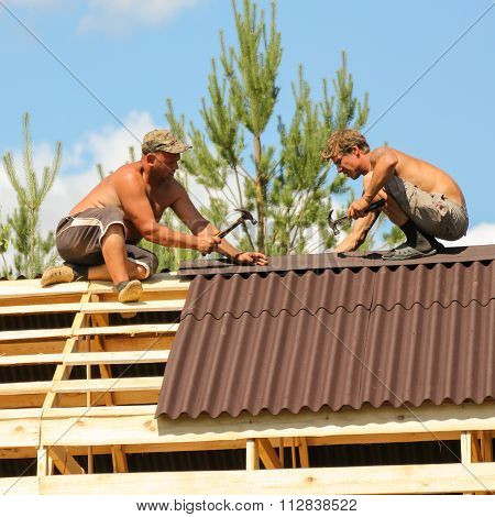 Two Workers With A Hammer In His Hands On The Roof.