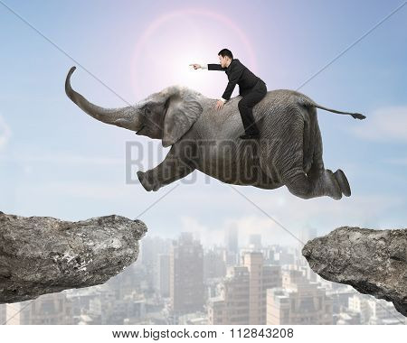 Man With Pointing Finger Riding Elephant Flying Over Two Cliffs