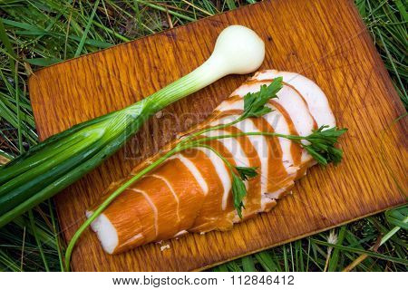 tourist food, onion and bacon, on hardboard in green grass