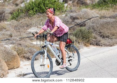 People Going By Bike In The City In Milos, Greece. A Lot Of Tourists Prefer Using Bike Instead Of Ca