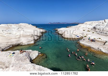 Tourists Enjoy The Clear Water Of Sarakiniko Beach In Milos, Greece. This Beach Is One Of The Most B