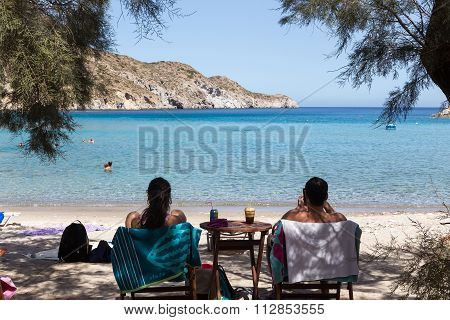 Rear View Of Tourists Enjoying The View Of Adamas Beach On Milos Island, Greece.
