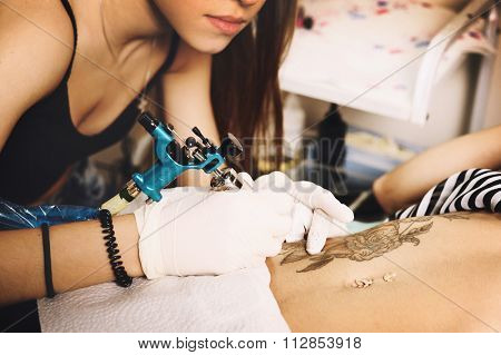 Woman tattooer making floral tattoo with black roses design on a girl stomach with pierced navel on it.