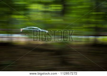 Car going fast on a hughway (motion blurred image) poster