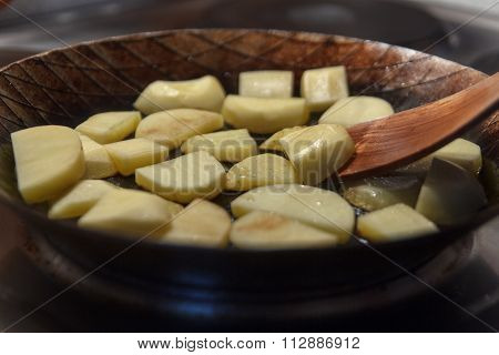 Raw chip potatoes in iron frying pan with spatula