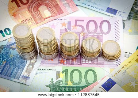 Decreasing stacks of euro coins on euro banknotes