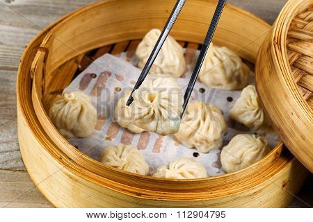 Freshly Steamed Chinese Pork Buns Being Taken Out Of Bamboo Steamer Ready To Eat