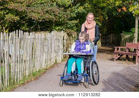 Disability a disabled child in a wheelchair relaxing outside together with a care assistant poster
