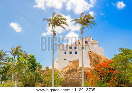 Colonial Building On Top Of The Mountain With Coconut Palms And Native Trees On Sunny Day