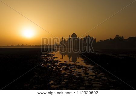 The beautiful view of Taj Mahal during sunrise with reflection from the Yamuna river Agra India.