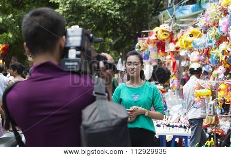 Asian cameraman filming a female journalist on site