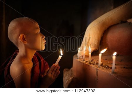 Portrait of young novice monk praying with candlelight inside a Buddhist temple, low light setting, Bagan, Myanmar.