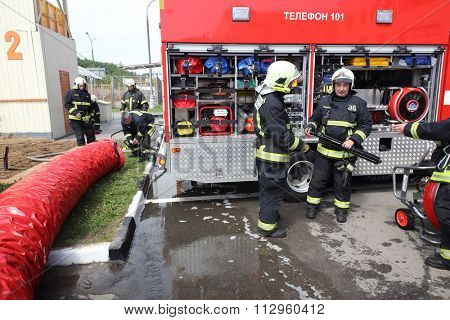 RUSSIA, MOSCOW - MAY 29, 2015: A man working with large tube near fire truck with equipment on territory of fire station.