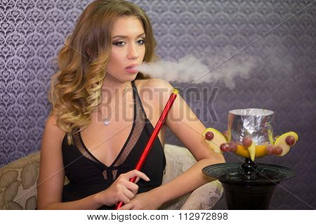 Beautiful girl in black dress with decollete exhale smoke on the hookah room