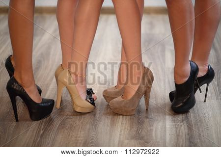 Four pair beautiful female legs with high-heeled shoes
