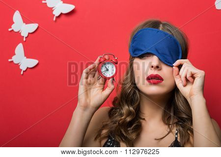 Beautiful woman in pajamas cami top and alarm clock poster