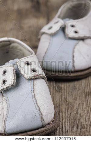 old vintage baby shoes on a wooden surface closeup
