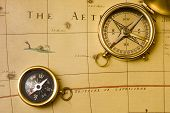 old style brass compass on antique map poster