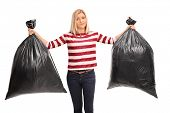 Displeased young woman holding two black trash bags and looking at the camera isolated on white background poster