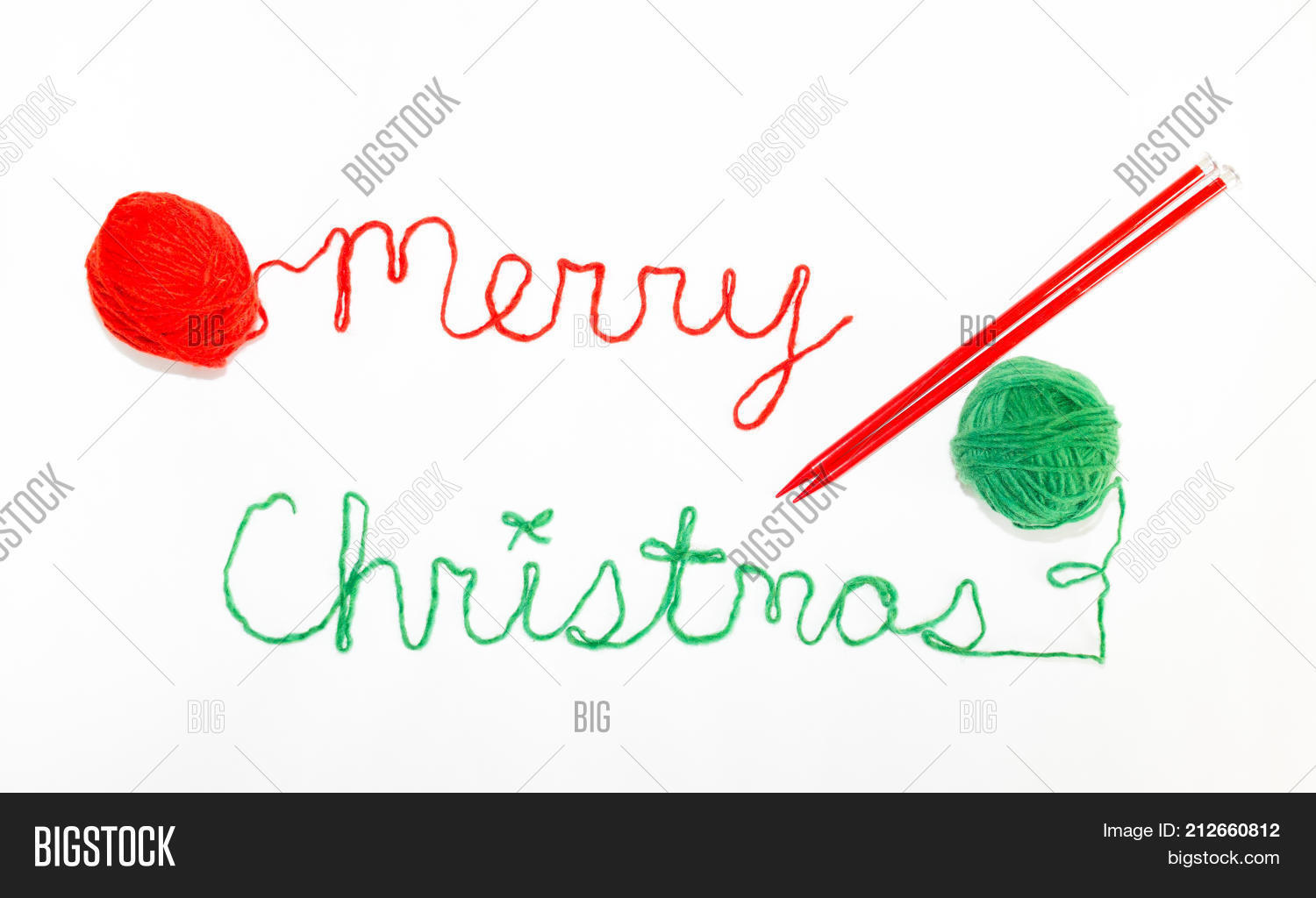 merry christmas written in cursive with red and green yarn and photographed from above against a