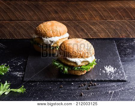 Two homemade fish burger on a shale black board