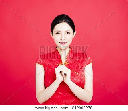 Asian woman in chinese cheongsam with congratulation gesture