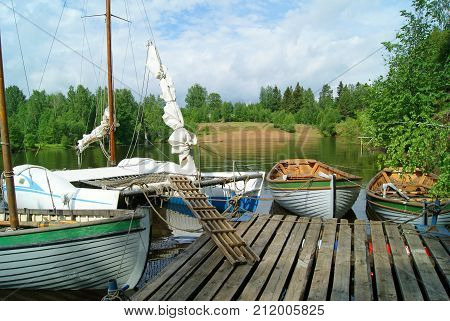 Four small sailing boats (one of which is a catamaran and two with masts removed) are moored at the pier in a quiet bay with green beaches