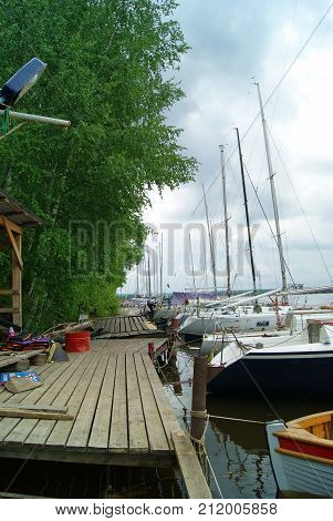 outgoing wooden pier along a wooded shore and a row of sailing yachts moored along it