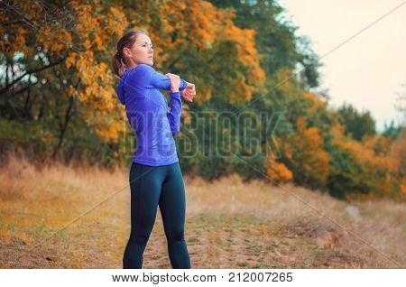 Caucasian Athletic Girl Performs Warming-up  Before Jogging On The Colorful Autumnal Forest