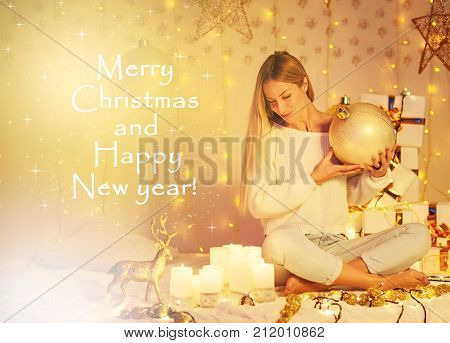 Merry Christmas and Happy New Year! beautiful young woman with long hair in knitted sweater sitting indoor decorated lights candles gifts balls stars. Magic Miracle golden atmosphere. People holiday