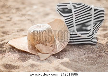 Straw hat bag on a tropical sand beach sunny day. Relax concept.