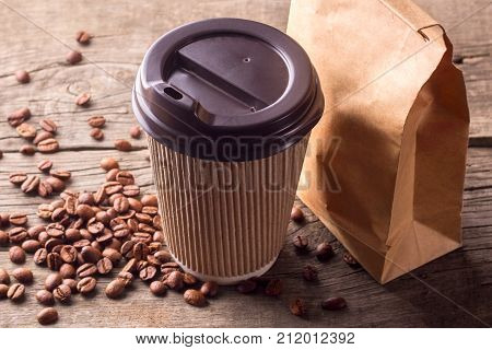 Coffee and snack for breakfast. A cup of coffee and a paper bag with a snack on a wooden table