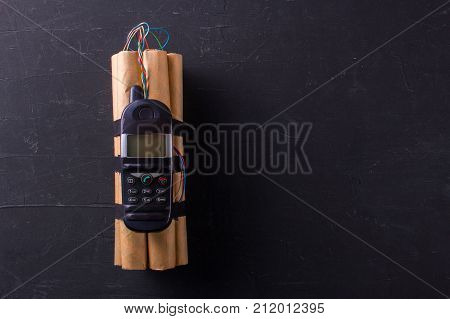 Bomba with explosives and detonator phone. The denamite sticks are connected by wires with a phonemon. Terrorism. Black background. Copy space for text