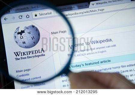 Paris, France - October 19, 2017 : Wikipedia Homepage On The Computer Screen Under Magnifying Glass.