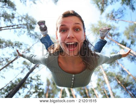 Woman falls from above the pine forest directly at you.