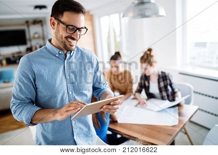 Portrait of handsome young male manager using digital tablet