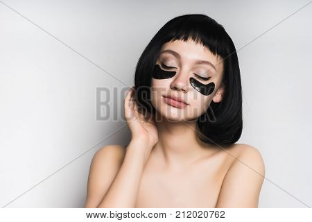 young beautiful girl with short black hair and black silicone patches under the eyes, sits with closed eyes